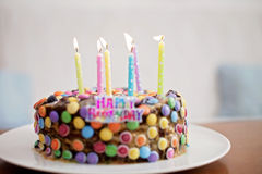 Happy Birthday sign and candles on child candy cake Royalty Free Stock Photos