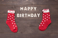 Happy Birthday and socks are on wooden background Stock Photo