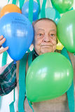 Happy birthday surprise party. Surprise birthday party theme. A humourous image showing crepe paper streamers and ballons dropping on an elderly man royalty free stock image