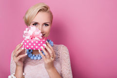 Happy birthday. Sweet blonde woman holding small gift box with ribbon. Soft colors. Studio portrait over pink background Royalty Free Stock Image