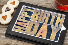 Happy birthday on tablet with tea and cookies. Happy birthday typography - isolated text abstract in letterpress wood type printing blocks on a digital tablet stock images