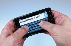 Happy Birthday Text. Thumbs texting Happy Birthday  to you!! on a smartphone Royalty Free Stock Photography
