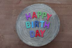 Happy Birthday text with colored wooden letters on a mango wooden round board royalty free stock images