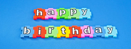 Happy birthday text message. In white lower case letters on colorful jigsaw style pieces isolated on blue background royalty free stock photography
