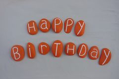 Happy Birthday text with orange painted stones over white sand stock photos