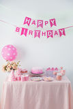 Happy birthday theme. Portrait of happy birthday flag banner chain and a table with full of sweet candy and cake Royalty Free Stock Photography