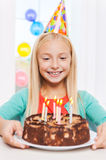 Happy birthday to me!. Happy little girl looking at the birthday cake and smiling Royalty Free Stock Images