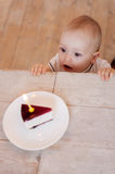 Happy birthday to me!. Top view of cute little baby looking at the plate with cake on it and keeping mouth open Stock Photography