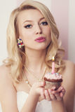 Happy birthday to you!. Beautiful blonde woman celebration with muffin and candle Royalty Free Stock Image