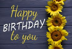 Happy Birthday to You. Birthday greeting card with flowers on a wooden background. Greeting card for girls