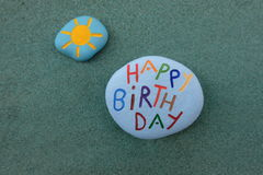 Happy Birthday under the sun, painted stones for a conceptual composition over the green sand Royalty Free Stock Photography