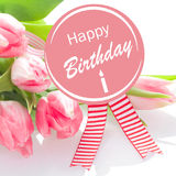 Happy Birthday wishes. On a round pink rosette with colourful striped ribbons with a gift of a bouquet of natural fresh pink tulips for a loved one or royalty free stock photos