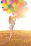 Happy birthday woman against the sky with rainbow-colored air ba Royalty Free Stock Photos