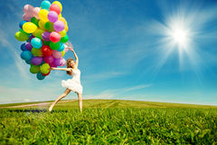 Happy birthday woman against the sky with rainbow-colored air ba. Lloons in hands. sunny and positive energy of nature. Young beautiful girl on the grass in the stock images