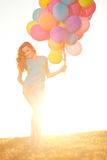 Happy birthday woman against the sky with rainbow-colored air ba Stock Photos