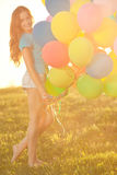 Happy birthday woman against the sky with rainbow-colored air balloons. In hands. sunny and positive energy of nature. Young beautiful girl on the grass in the Royalty Free Stock Photography