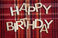 Happy birthday words written with wooden letters on red textile material with colored stripes, top view, flat lay