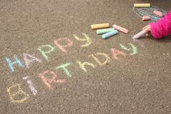 Happy birthday written in colored crayons on the sidewalk