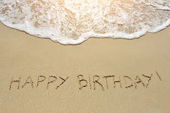 Happy birthday written on sand beach Royalty Free Stock Photos