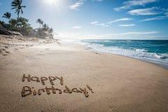 Happy Birthday written in the sand