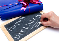 Happy birthday written on a slate blackboard with a gift Royalty Free Stock Photos