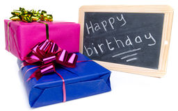 Happy birthday written on a slate blackboard with gifts Royalty Free Stock Image