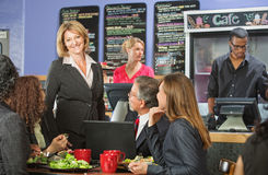 Happy Bistro Owner With Customers Royalty Free Stock Images