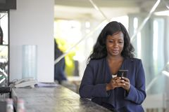 Happy black african american woman working from restaurant bar texting on internet mobile phone stock photos
