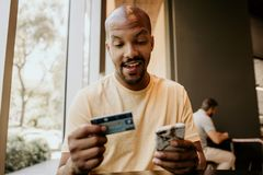 Happy Black african man holding hands credit card and mobile phone. Technology, internet banking, e-commerce and online stock photo