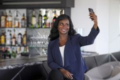 Happy black afro american woman in casual elegant clothes taking selfie portrait photo with mobile phone Royalty Free Stock Photos