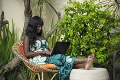 Happy black afro american woman in elegant dress working on luxury terrace villa with laptop excited and happy Royalty Free Stock Photography