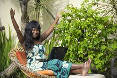 Happy black afro american woman in elegant dress working on luxury terrace villa with laptop excited and happy Royalty Free Stock Photo