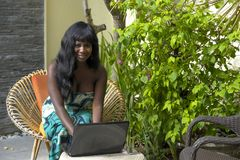 Happy black afro american woman in elegant dress working on luxury terrace villa with laptop excited and happy Stock Photo