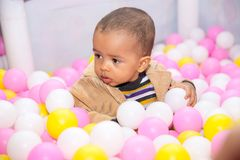 Happy black boy in colored ball on birthday on playground. Stock Photos