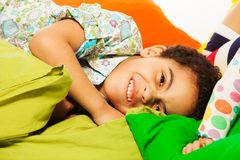 Happy black boy laying on the pillows Royalty Free Stock Image