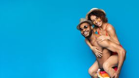 Happy black boyfriend piggybacking his cheerful girlfriend. Both wearing swimsuits, blue panorama background with free space stock photo