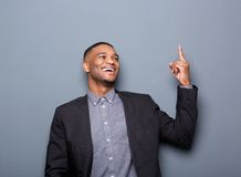 Happy black business man pointing finger. Portrait of a happy black business man pointing finger on gray background Royalty Free Stock Photos