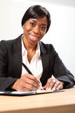 Happy black business woman signing document Stock Photo