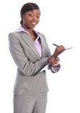 Happy black business woman writing on clipboard Royalty Free Stock Photos