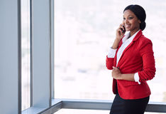 Happy black businesswoman smiling while talking on her mobile cellphone Royalty Free Stock Images
