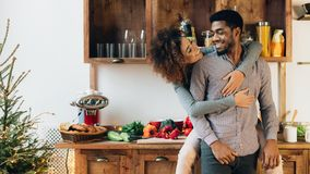 Loving african-american couple enjoying time together in kitchen. Happy black couple embracing and having fun at kitchen, panorama, copy space stock image