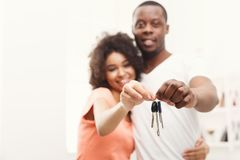 Happy black couple holding keys of their new home. Key of new home. Happy african-american young couple standing close to each other and smiling while holding Royalty Free Stock Photos
