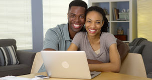 Happy black couple with laptop and bills Stock Photography