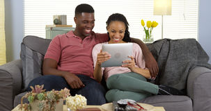 Happy black couple laughing and using tablet Stock Images