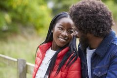 Happy black couple leaning on a fence in the countryside looking into each other�s eyes, close up royalty free stock photography