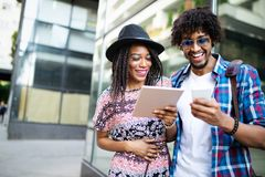 Happy black couple watching media in a digital table outdoor stock photo