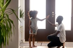 Happy black dad and little daughter giving high-five in hallway royalty free stock images