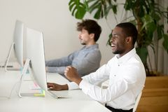 Happy black employee excited by online win or good result. Happy black employee excited by win looking at computer watching game online in office, african winner royalty free stock images