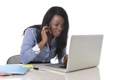 Happy black ethnicity woman working at computer laptop and mobile phone relaxed. Young attractive and black African American ethnicity woman working at computer royalty free stock photos