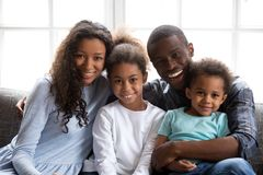 Happy black family of four looking at camera at home. Happy black family of four dad mom and little son daughter, loving african mother father embrace 2 mixed stock photos